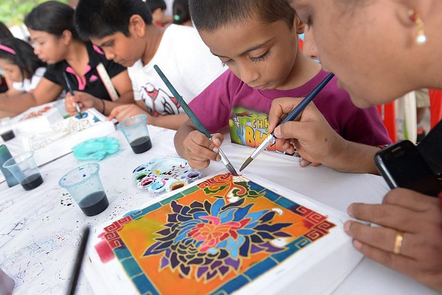From left, Mdm Chokkakula Mahalakshmi, 38 and her son Chokkakula Satvik, 5, painting at PAssionARTS Village: Memories & Dreams, organised by the Community Arts and Culture Cluns in Nee Soon GRC, at Nee Soon Central Hardcourt, May 30, 2014. -- ST