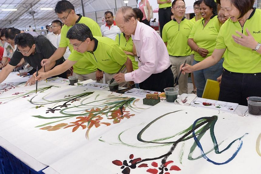 A live demonstration of Chinese painting on a 11.5m long rice-paper by Mr Tan Khim Ser (second from right), President of Life Art Society at Nee Soon Central Hardcourt, May 30, 2014. -- ST PHOTO: LIM SIN THAI