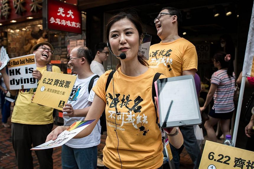Pro democracy activists distribute leaflets outside a polling station in Hong Kong on June 22, 2014. -- PHOTO: AFP