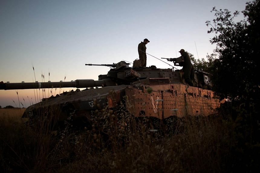 Israeli soldiers are seen on their Merkava tank positioned near the Quneitra checkpoint on the border with Syria in the Israeli-annexed Golan Heights, on June 22, 2014. -- PHOTO: AFP