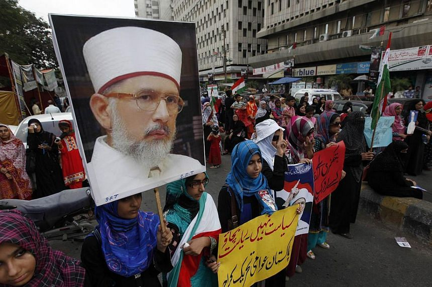 Female supporters of Tahirul Qadri, a Sufi cleric and the leader of the Awami Tehreek political party, hold his portrait during a protest in Karachi, condemning the deaths of their party's workers in Lahore on June 19, 2014. -- PHOTO: REUTERS