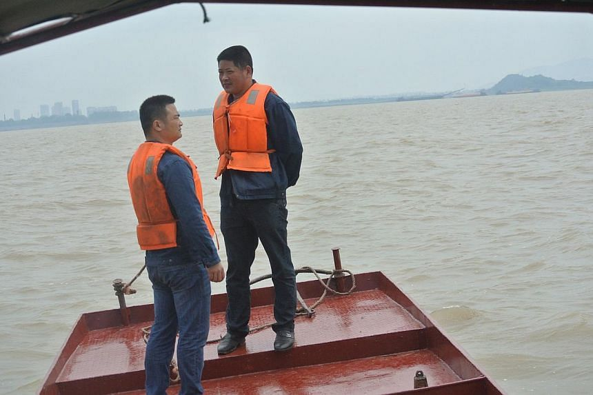 This picture taken on May 9, 2014 shows Liu Bo (right), a member of River Porpoise Protection Society, talking to another porpoise patroller Chen Hanbo on a boat at Dongting Lake in Yueyang, east China's Hunan province. -- PHOTO: AFP