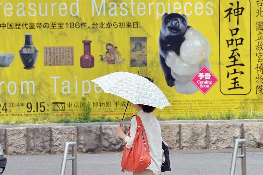 A visitor walks past a billboard advertising an exhibition of treasured masterpieces on loan from the Taipei National Palace Museum at Japan's national museum in Tokyo on June 23, 2014. Taiwan's first lady has postponed a rare visit to Japan after a