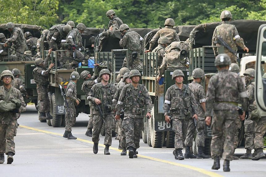 South Korean soldiers get in their military vehicles as they take part in a search and arrest operation near the area of a standoff between troops and a conscript soldier who shot and killed five comrades in Goseong on June 23, 2014.A South Kor