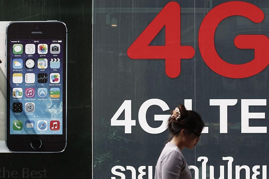 A woman walks past a billboard advertising 4G at a shopping district in Bangkok on June 20, 2014. Thailand's telecoms sector is fast emerging as the first economic casualty of an interventionist junta. -- PHOTO: REUTERS
