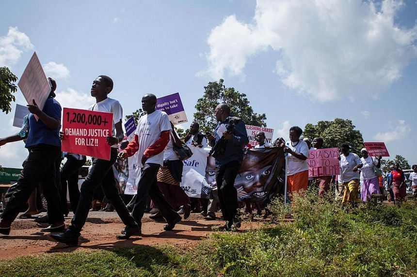 "A protester holds a sign reading ""1,200,000+ demand justice for Liz"", as he takes part in a march through the Kenyan border town of Busia, on June 23, 2014, The trial of a man accused of carrying out a brutal gang rape of a schoolgirl, who was m"
