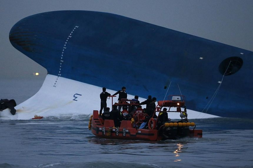 """Maritime police search for missing passengers in front of the South Korean ferry """"Sewol"""" which sank at the sea off Jindo in this April 16, 2014 file photo.Dive teams on Tuesday recovered another victim of South Korea's ferry disaster, the first"""