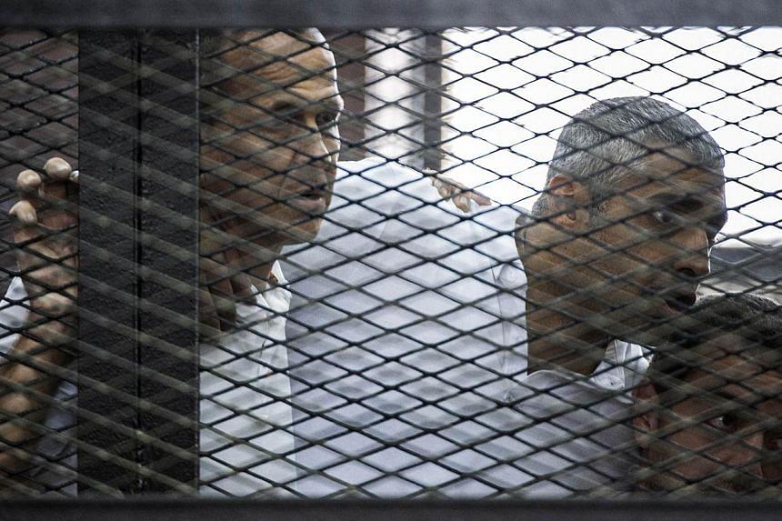 (From left) Al-Jazeera news channel's Australian journalist Peter Greste and his colleagues, Egyptian-Canadian Mohamed Fadel Fahmy and Egyptian Baher Mohamed, listen to the verdict inside the defendants cage during their trial for allegedly supportin