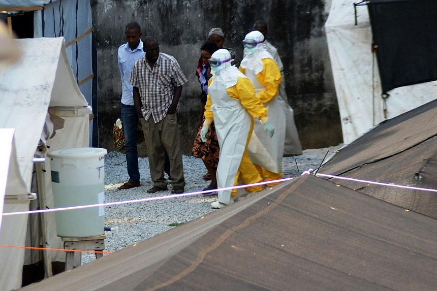Health workers, wearing protective suits, walking in an isolation center for people infected with Ebola at Donka Hospital in Conakry on April 14, 2014. -- PHOTO: AFP