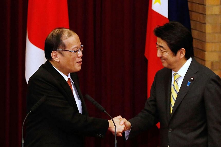 Philippines President Benigno Aquino (left) shakes hands with Japan's Prime Minister Shinzo Abe (right) during a joint news conference at the prime minister's official residence in Tokyo on June 24, 2014.Japan and the Philippines on Tuesday, Ju
