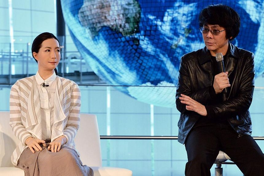 """Osaka University professor Hiroshi Ishiguro (right) introduces a new female humanoid robot named """"Otonaroid"""" to the media at the National Museum of Emerging Science and Technology in Tokyo on June 24, 2014. -- PHOTO: AFP"""