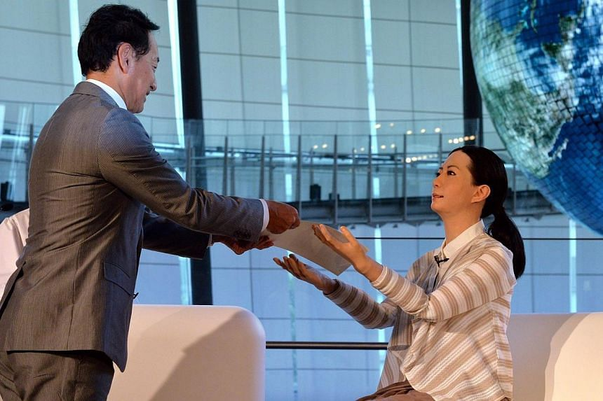"""Former astronaut and the director of the museum, Mamoru Mori (left), gives an appointment letter for the museum staff to the new female humanoid robot named """"Otonaroid"""" as she is introduced to the media at the National Museum of Emerging Science and"""