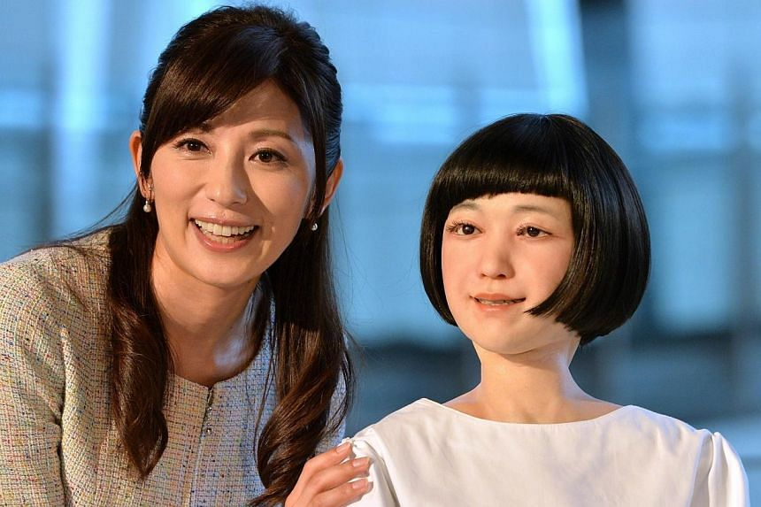 """Japanese announcer Aki Nakata (left) smiles as she poses with a new humanoid robot named """"Kodomoroid"""" (right) at the National Museum of Emerging Science and Technology in Tokyo on June 24, 2014.Japanese scientists on Tuesday, June 24, 2014, unv"""