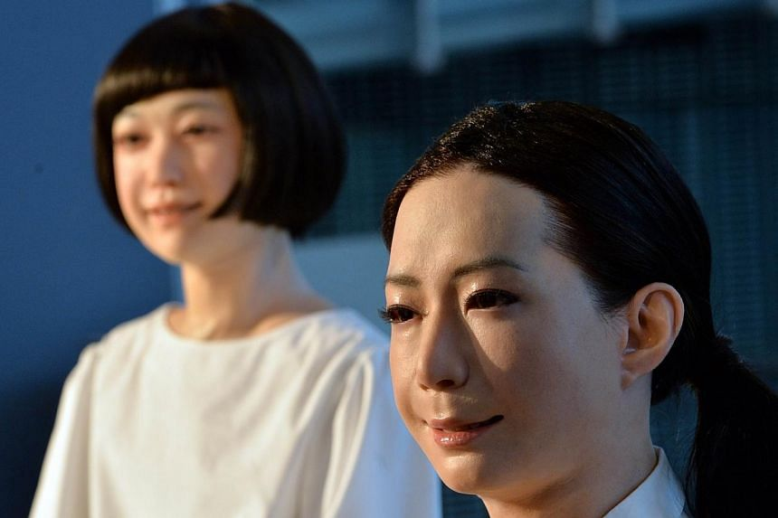 """The new humanoid robots named """"Otonaroid"""" (right) and """"Kodomoroid (left) are pictured during a press preview at the National Museum of Emerging Science and Technology in Tokyo on June 24, 2014. -- PHOTO: AFP"""