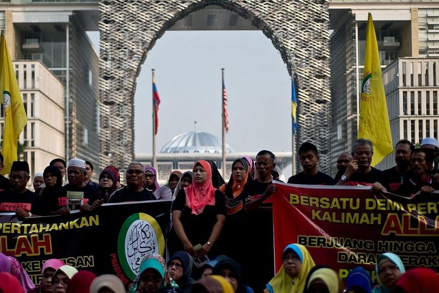 """Malaysian Muslim activists wait for the verdict outside Malaysia's highest court in Putrajaya on June 23, 2014.Human rights group Amnesty International on Tuesday, June 24, 2014, condemned a Malaysian government ban on Christians using """"Allah"""""""