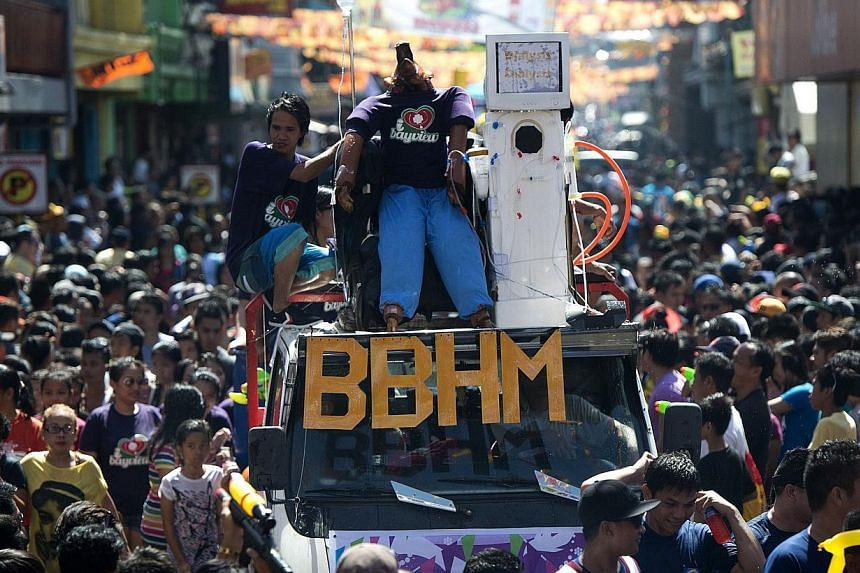 A roasted pig (centre) dressed as a dialysis patient is paraded through the streets in Balayan, Batangas province, south of Manila on June 24, 2014, to celebrate the feast of St. John the Baptist. -- PHOTO: AFP