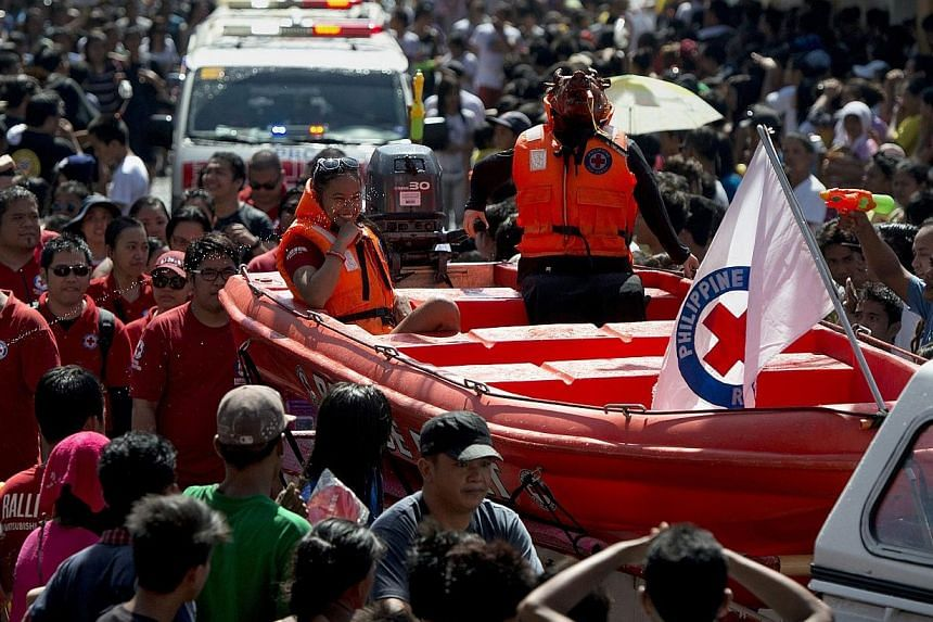 A roasted pig (centre right) dressed as a Red Cross rescue worker in a boat is paraded through the streets in Balayan, Batangas province, south of Manila on June 24, 2014, to celebrate the feast of St. John the Baptist. -- PHOTO: AFP