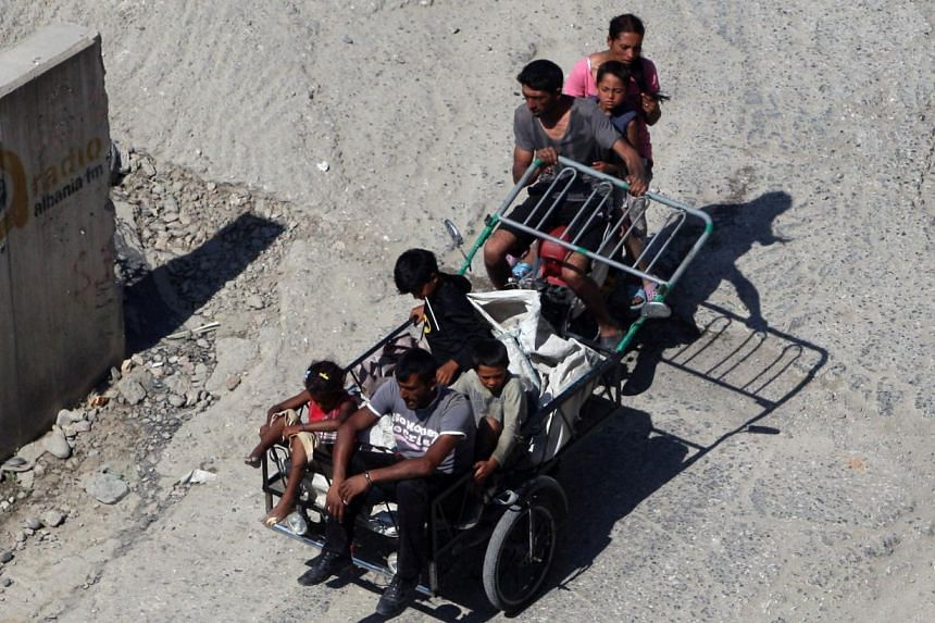 Members of a Roma family riding a tricycle packed with sacks to collect plastic and aluminum waste from rubbish bins for sale to the recycling industry in Albania's ca[ital city, Tirana. A chaotic transition to capitalism has left the former Sta