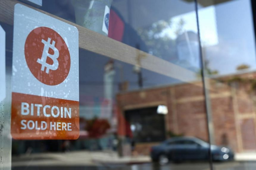 A bitcoin sticker in the window of a convenience store in Los Angeles, California. A new Bill passed by lawmakers would repeal what backers say is an outdated law prohibiting commerce using anything but US currency. PHOTO: REUTERS
