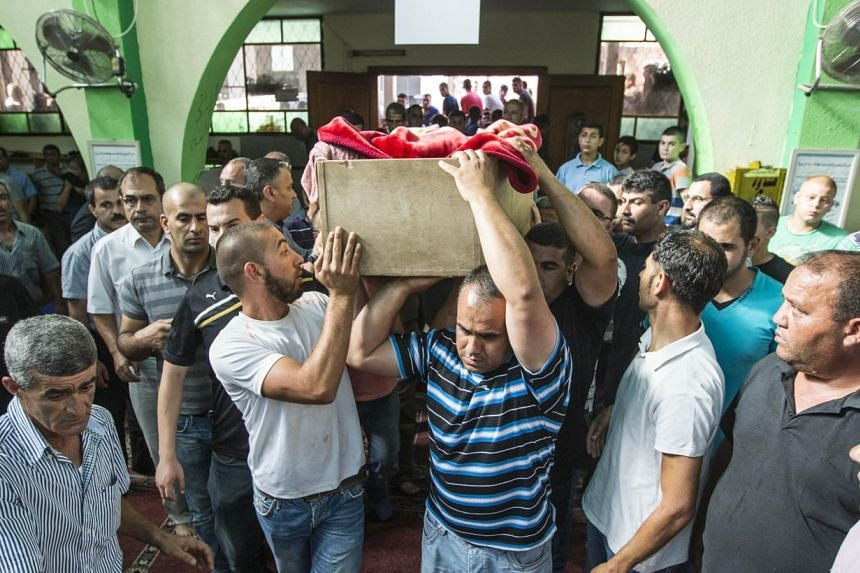 Relatives of Arab Israeli youth Mohammed Qaraqara,13, carrying his coffin during his funeral in the northern Israeli village of Arrabe on Monday. The son of a defence ministry contractor, he was killed on the Golan Heights on Sunday when a missile hi