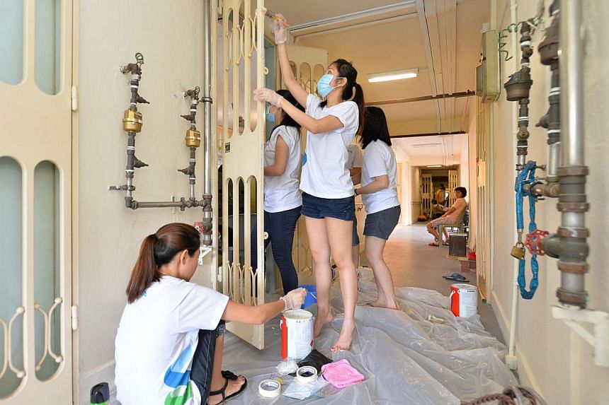 Volunteers from Standard Chartered Bank helping to paint the doors of a flat in Bukit Merah View yesterday. Project Fresh aims to help 1,900 households in six rental blocks. -- PHOTO: LIM YAOHUI FOR THE STRAITS TIMES