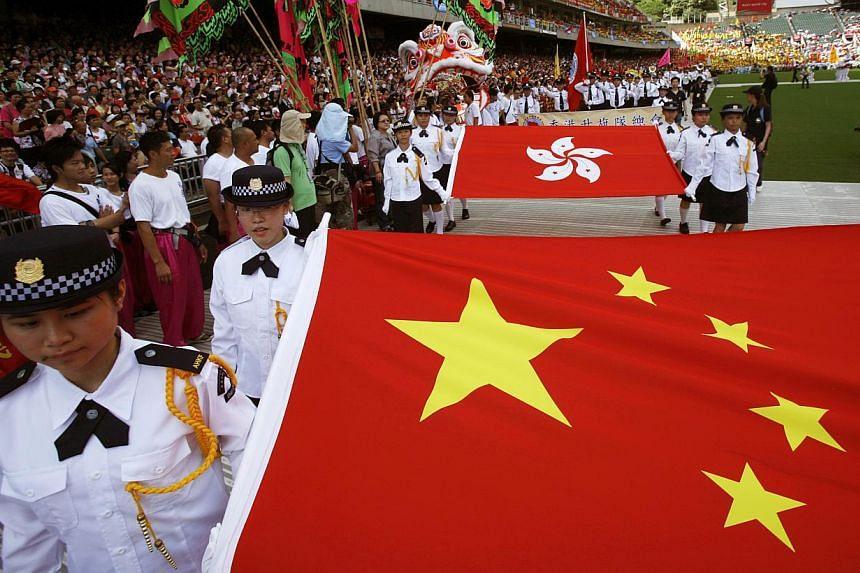 Students carrying a national flag of China (front) and a Hong Kong flag during a parade at a Hong Kong stadium in 2009.