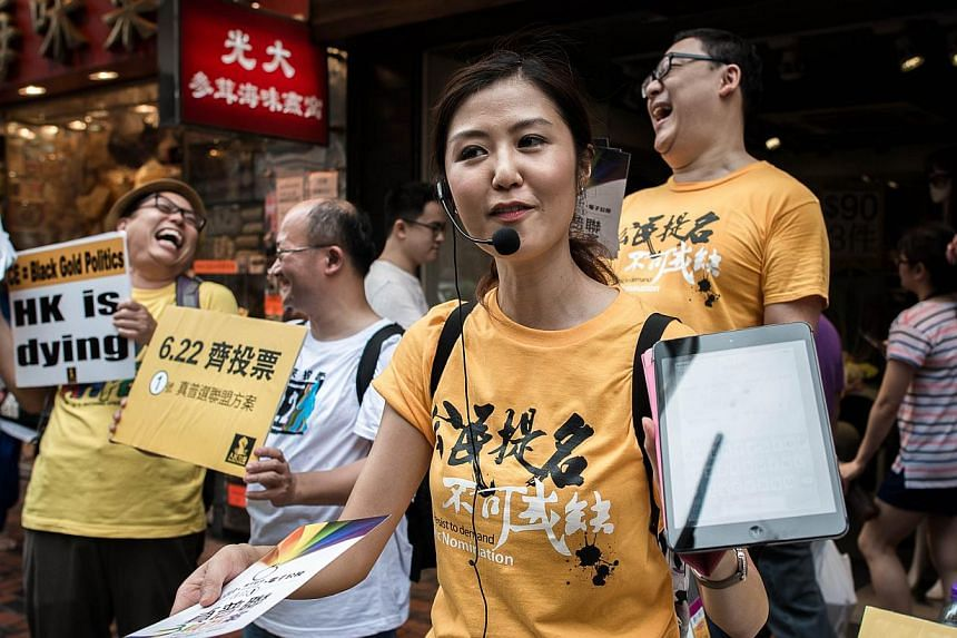 Pro-democracy activists distributing leaflets outside a polling station in Hong Kong on Sunday. China is enraged by an unofficial online poll in the territory for full democracy which has drawn nearly 700,000 Hong Kongers so far.