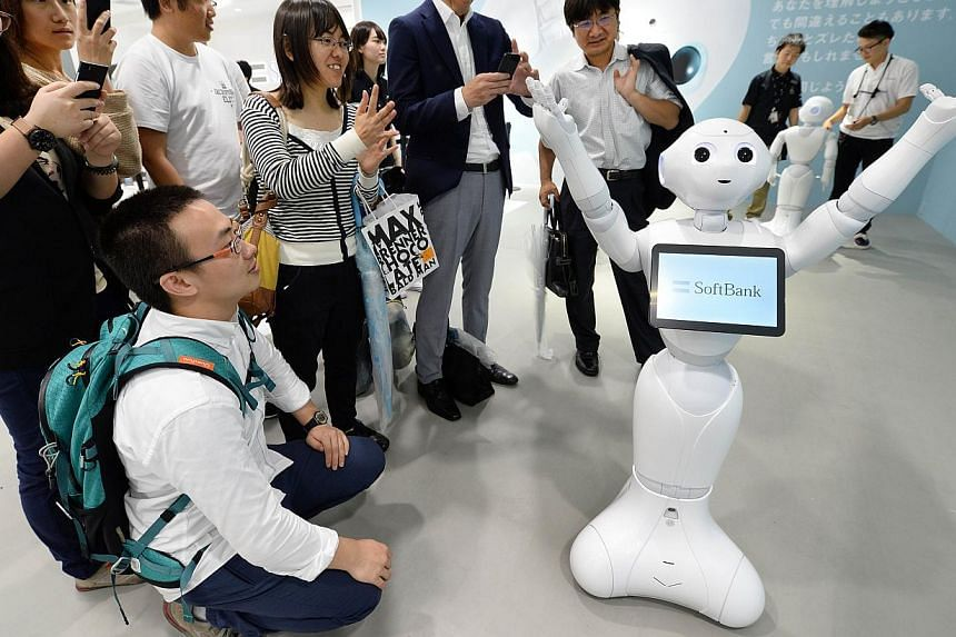 People look at humanoid robot 'Pepper', which is jointly developed by Japan's mobile carrier SoftBank and French humanoid robot maker Alderbaran, at a showroom of SoftBank in Tokyo on June 6, 2014. Softbank will release the robot next February with a