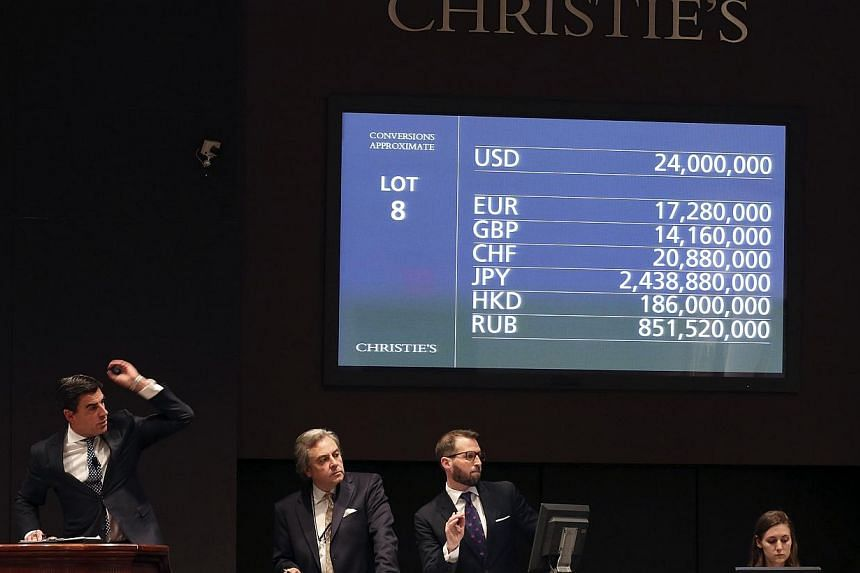"""A Christie's moderator facilitates the sale of an artwork titled """"Nympheas"""" by artist Claude Monet during a Christie's auction in New York May 6, 2014.An iconic Water Lilies painting by French artist Claude Monet sold for £31.7 million (S$67 m"""