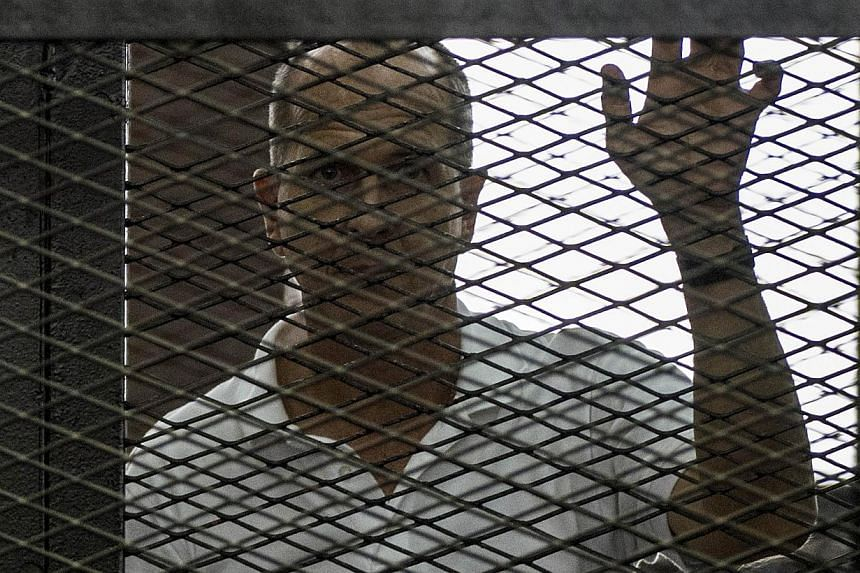 Al-Jazeera news channel's Australian journalist Peter Greste (C) listens to the verdict inside the defendants cage during his trial for allegedly supporting the Muslim Brotherhood on June 23, 2014 at the police institute near Cairo's Tora prison.&nbs