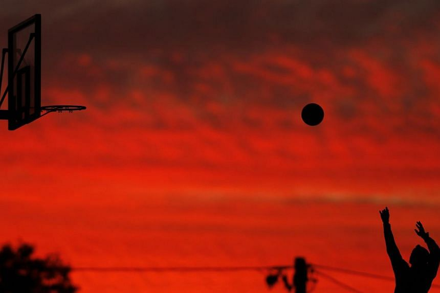 A boy throws to the basket as the setting sun illuminates low clouds at an outdoor basketball court in Sydney's beachside suburb of Cronulla, on June 12, 2014.According to Australia's Bureau of Meteorology, Sydney has recorded its warmest May o