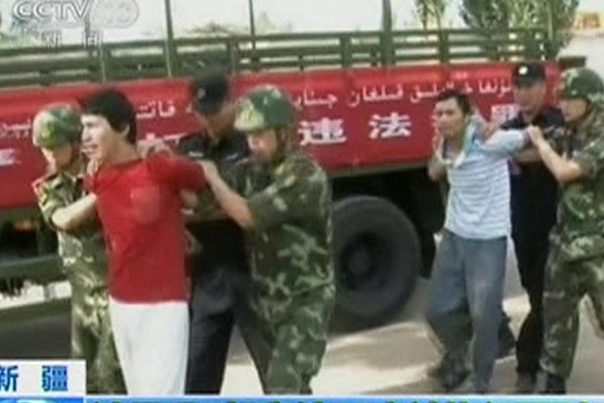 Men who are about to be executed are escorted by riot policemen outside in this still image taken from video in an unknown location in the Xinjiang Uighur Autonomous Region, on June 16, 2014. Chinese state television on Tuesday showed dramatic f