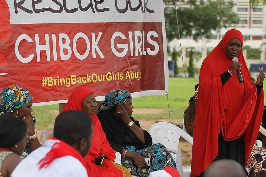 A member of the #BringBackOurGirls Abuja campaign group addresses a sit-in protest at the Unity Fountain in Abuja on June 18, 2014. Suspected Boko Haram militants have abducted more than 60 women and girls, some as young as three, in the latest