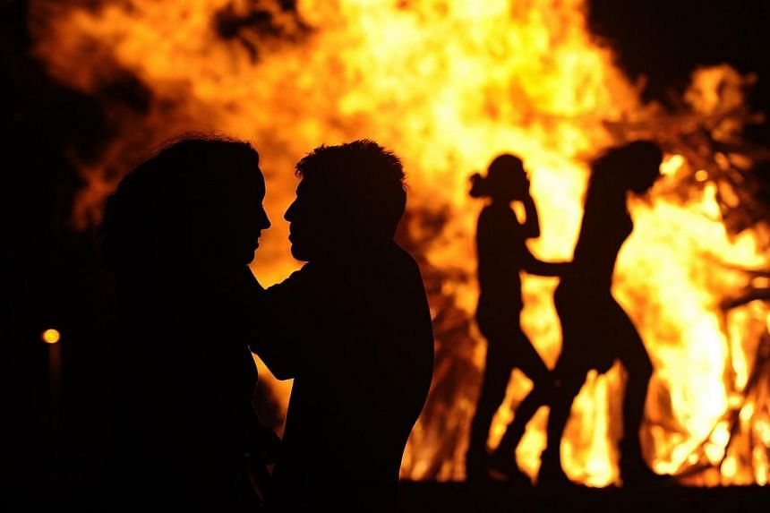 People attend a party held during the night of the San Juan bonfire on the beach of Playa de Poniente in Gijon early June 24, 2014. Fires formed by burning unwanted furniture, old schoolbooks, wood and effigies of malign spirits are seen across Spain
