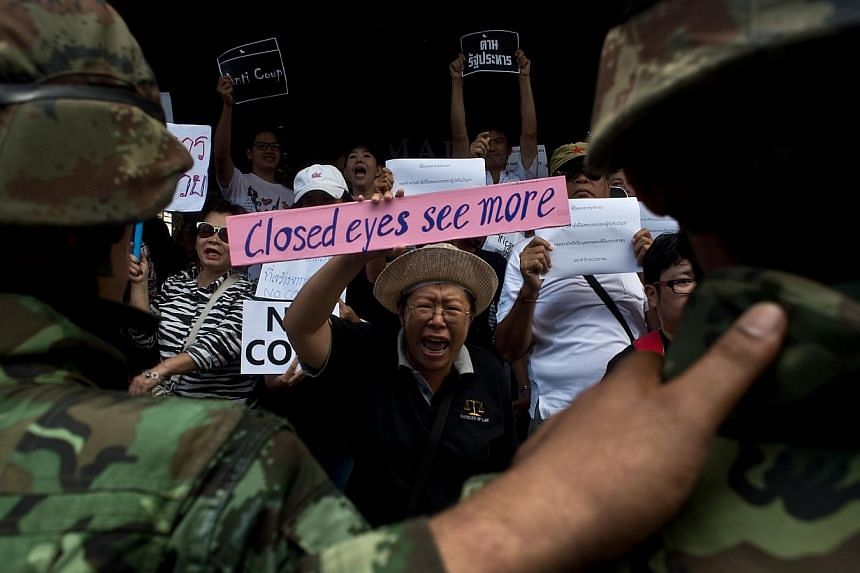 An anti-coup protester (centre) holds a placard as they are blocked by Thai Army soldiers during a protest in Bangkok on May 24, 2014.The former president of the toppled Thai ruling party on Tuesday launched the first official opposition group