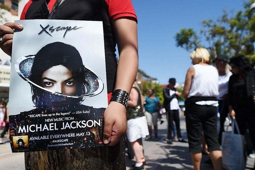 A dancer holds a poster for Xscape, the second posthumous compilation album of previously unreleased songs by Michael Jackson, after a Michael Jackson tribute flash mob dance on the 3rd Street Promenade in Santa Monica, California, on June 22, 2014.