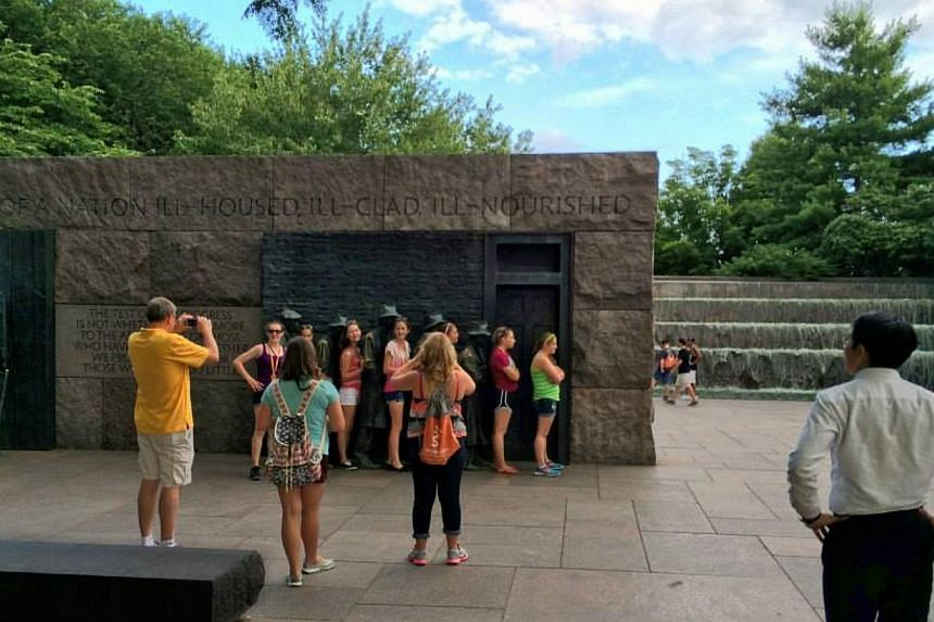 Visitors to the FDR Memorial pose for a photo with the sculpture of a unemployed people queuing up for dole during the Great Depression. Prime Minister Lee Hsien Loong visited the landmark while on a visit to the US. -- PHOTO: MCI