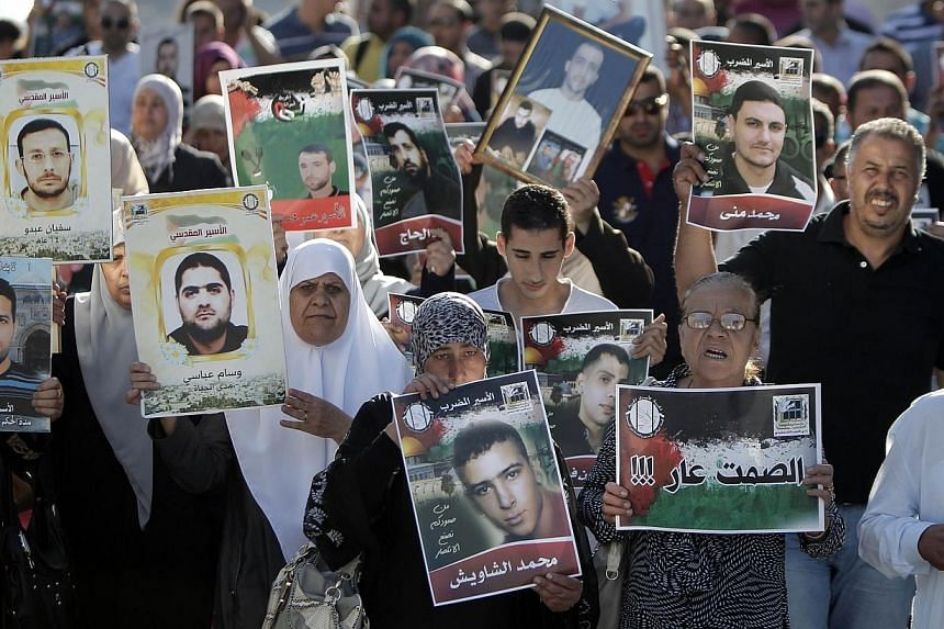Palestinians hold posters with slogans and portraits of detainees during a demonstration on June 10, 2014, outside the Red Cross building in Jerusalem in support of Palestinian prisoners in Israeli jails who were on hunger strike.Sixty-three Pa