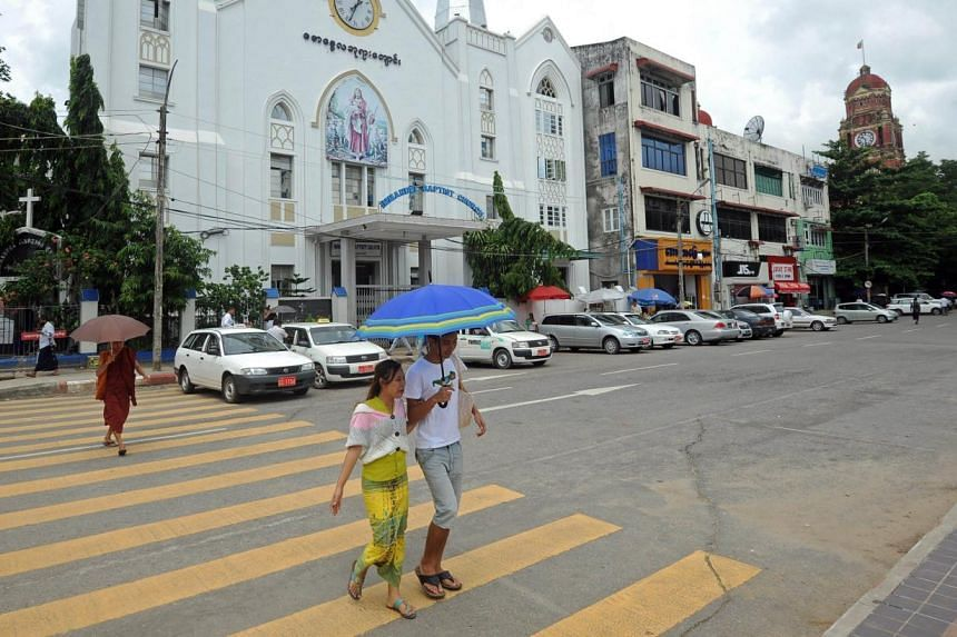 A couple crossing a road before a church in Yangon. Proposals by radical Buddhist monks to criminalise inter-faith marriage in Myanmar face strong opposition from women's rights groups in a tussle over the nation's religious identity that has sparked
