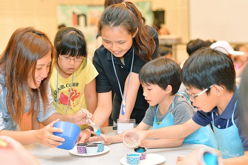 Young participants of the chemistry baking session included Chloe Ho (in yellow), seven, Talon Lee (in grey), six, and Dylan Ho (in blue), nine, seen here getting help to decorate their cupcakes.