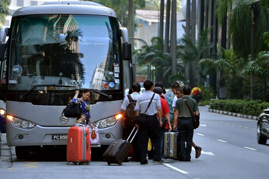 A tour group boarding a bus (above). A coroner's inquiry into the death of three-year-old Kryshan Nirmal Kumar (facsimile of ST story left), who was run over by a bus, has suggested that the placement and design of blind spot mirrors for buses should