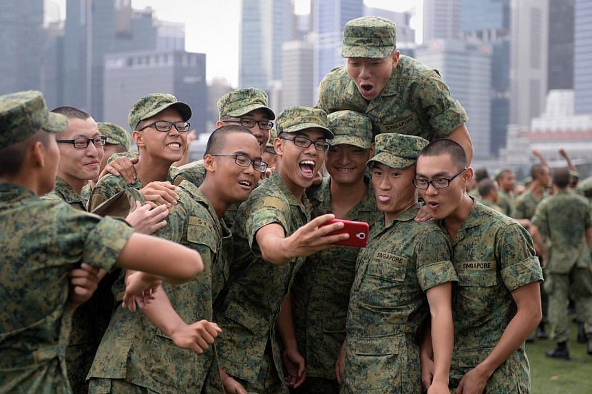 Recruits celebrating after their Basic Military Training passing out parade held at the Floating Platform@Marina Bay in April. -- ST PHOTO: MARK CHEONG