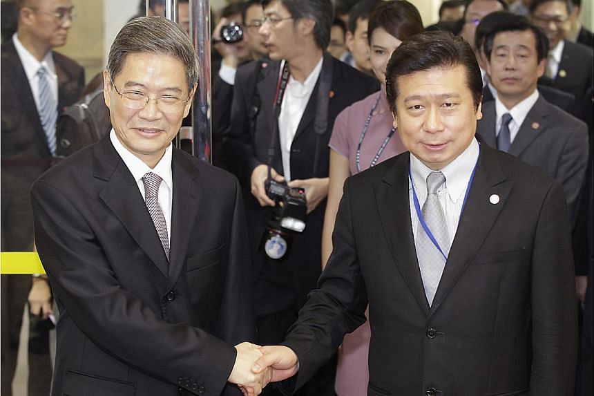 Mr Zhang Zhijun (left), director of China's Taiwan Affairs Office, shakes hands with Mainland Affairs Council Vice Minister Chang Hsien-yao, after arriving at Taoyuan International Airport, northern Taiwan on June 25, 2014. -- PHOTO: REUTERS