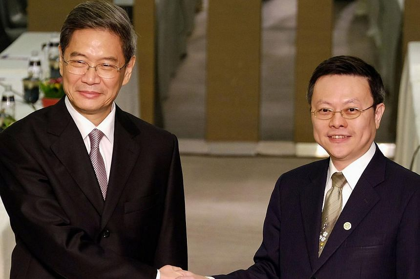 Chinese official Zhang Zhijun (L), director of the Taiwan Affairs Office, shakes hands with his Taiwanese counterpart Wang Yu-chi, director of Taiwan's Mainland Affairs Council (MAC), at a hotel in Taoyuan on June 25, 2014. -- PHOTO: AFP