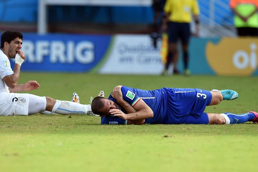 Uruguay's forward Luis Suarez (left) reacts past Italy's defender Giorgio Chiellini during a Group D football match between Italy and Uruguay at the Dunas Arena in Natal during the 2014 FIFA World Cup on June 24, 2014. -- PHOTO: AFP