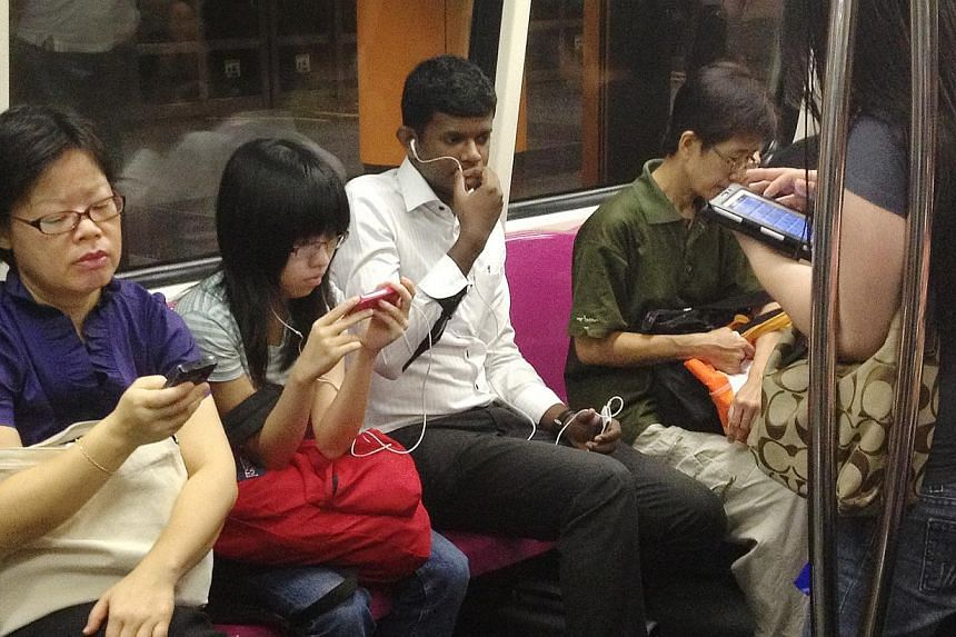 MRT commuters using their mobile devices in a MRT train on Oct 18, 2012. Software piracy is on the wane here partly due to computers falling out of favour with consumers, and the growing popularity of tablets. -- ST PHOTO: FILE