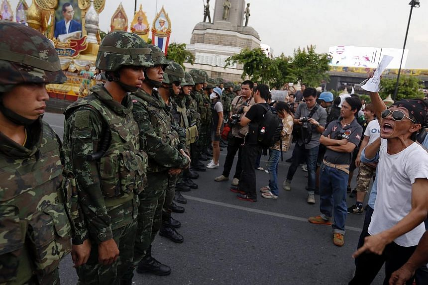 Protesters against military rule face soldiers at the Victory monument in Bangkok on May 26, 2014. -- PHOTO: REUTERS