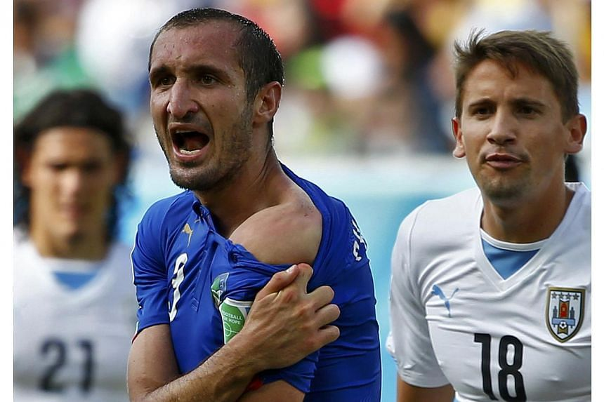 Italy's Giorgio Chiellini shows his shoulder, claiming he was bitten by Uruguay's Luis Suarez, during their 2014 World Cup Group D soccer match at the Dunas arena in Natal on June 24, 2014. -- PHOTO: REUTERS