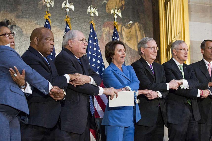 (From left) Rep Marcia Fudge, Rep John Lewis, Senate Carl Levin, House Minority Leader Nancy Pelosi, Senate Minority Leader Mitch McConnell, Senate Majority Leader Harry Reid and Speaker of the House John Boehner lock arms as they sing 'We Shall Over