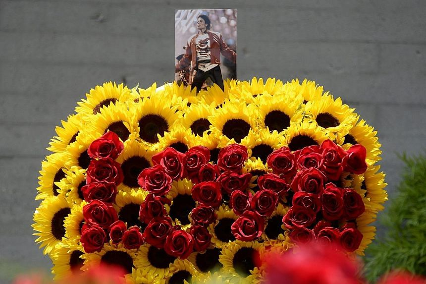 """A photograph of Michael Jackson is placed on top of heart shaped wreath with the word """"Love"""" in red roses along with thousands of red roses, purchased by Michael Jackson fans through online campaign, adorn the entrance of the mausoleum where Jackson"""